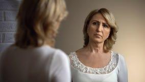 Gedeprimeerde oude vrouw die in witte kleding bezinning in spiegel bekijken, problemen royalty-vrije stock foto