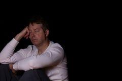 Gedeprimeerde rijpe mens die met zijn die ogen denken in donkere backg worden gesloten Stock Afbeeldingen