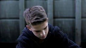 Gedeprimeerde tienerjongen die hopeloosheid voelen, die het verkeerde doen, verdriet betreuren stock afbeeldingen