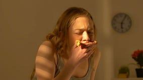 Gedeprimeerde tienermeisje greedily het kauwen snoepjescake, fuif die wanorde, boulimie eten stock video