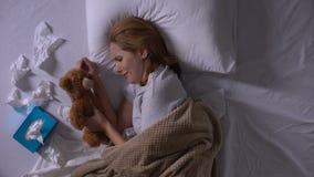 Gedeprimeerde vrouw in bed die, koesterend teddybeer, die aan mislukking lijden schreeuwen stock videobeelden