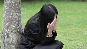 Gedeprimeerde vrouw dichtbij de boom in het park stock video