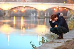 Gedeprimeerde vrouw die door de waterkant in een stad knielen dichtbij een en brug die eenzaam schreeuwen voelen stock afbeeldingen