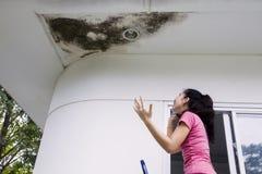 Gedeprimeerde vrouw met beschadigd plafond stock fotografie