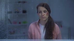 Gedeprimeerde vrouw met gewonde gezichtszitting achter regenachtig venster, aanval stock footage
