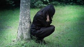 Gedeprimeerde vrouw in nadruk dichtbij boom in het park stock videobeelden