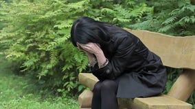 Gedeprimeerde vrouw op bank in het park stock videobeelden