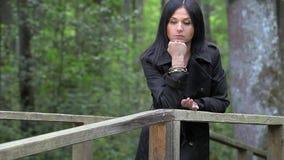 Gedeprimeerde vrouw op de brug in het park stock videobeelden