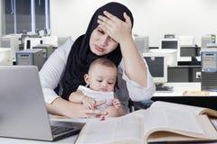 Gedeprimeerde vrouwelijke werknemer met baby in bureau Stock Fotografie