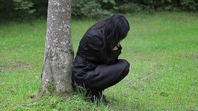 Gedeprimeerde vrouwenzitting dichtbij de boom in het park stock videobeelden