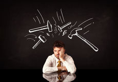 Gedeprimeerde zakenmanzitting onder hamertekens stock afbeelding