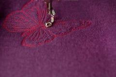 Gedetailleerd borduurwerk van roze vlinder op purpere gekookte wol met een borduurwerkmachine royalty-vrije stock foto's