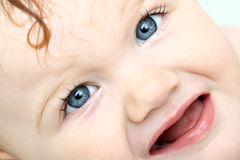 Gedetailleerd gezicht van boze blauw-eyed baby die bad neemt Stock Foto's