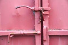Gedetailleerd klink en handvat op een rode ijzerdeur stock afbeelding