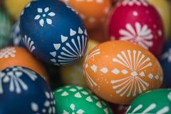 Gedetailleerd macroschot van met de hand geschilderde kleurrijke paaseieren in een decoratief nest stock afbeeldingen