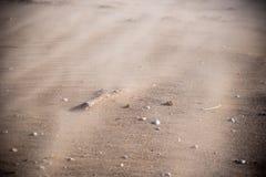 Gedetailleerde close-up die van zandstorm over strandoppervlakte blazen stock afbeelding