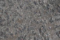 Gedetailleerde dichte omhooggaande oppervlakte van asfalt op straten met kleine stenen en barsten stock afbeelding