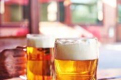 Gedetailleerde foto van twee glazen bier met wit schuim in garde stock afbeelding