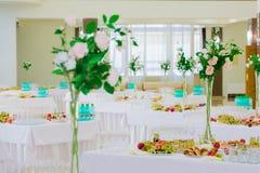 Gediende lijsten bij het Banket Desserts, fruit en gebakjes op het buffet Glaswerk en mineraalwaterflessen Rozen in een kruik royalty-vrije stock foto