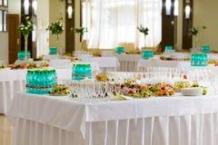 Gediende lijsten bij het Banket Desserts, fruit en gebakjes op het buffet Glaswerk en mineraalwaterflessen Rozen in een kruik stock fotografie