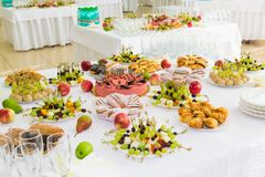 Gediende lijsten bij het Banket Desserts, fruit en gebakjes op het buffet Glaswerk en mineraalwaterflessen Rozen in een kruik royalty-vrije stock afbeeldingen
