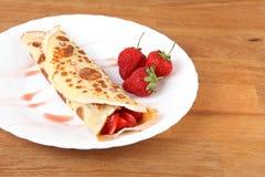 Gediende pannekoeken met aardbei en chocolade op witte plaat Stock Foto's