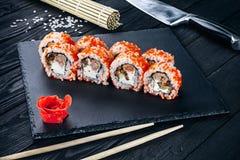 Gediende sushibroodjes op zwarte steen met eetstokjes Sluit omhoog mening over sushi op donkere achtergrond stock afbeeldingen
