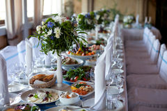 Gedient für eine Banketttabelle Weingläser mit Servietten, Gläser und Salate Lizenzfreie Stockfotografie