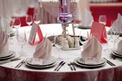 Gediente Tabelle mit Servietten, Karten und Gläsern auf dem Tisch Stockbilder