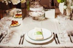 Gediente Tabelle mit Tellern, Gerät, Tischbesteck und Dishware auf Tischdecke lizenzfreie stockfotografie