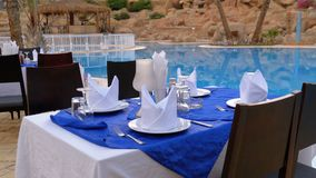 Gediente Tabelle nahe dem Swimmingpool mit blauem Wasser im Erholungsort von ?gypten stock video