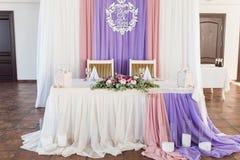 Gedienter Heiratsbankettisch im Restaurant verzierte weißes, rosa und purpurrotes Material, die weißen und rosa Blumen und Grün Stockfotos