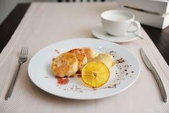 Gedientes Frühstück im Restaurant Hüttenkäsepfannkuchen mit orange Ringellocken und Kaffee Lizenzfreies Stockfoto