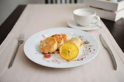 Gedientes Frühstück im Restaurant Hüttenkäsepfannkuchen mit orange Ringellocken und Kaffee Lizenzfreie Stockfotos