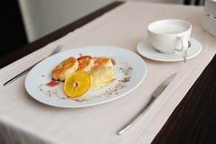 Gedientes Frühstück im Restaurant Hüttenkäsepfannkuchen mit orange Ringellocken und Kaffee Stockbild
