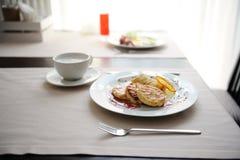 Gedientes Frühstück im Restaurant Hüttenkäsepfannkuchen mit orange Ringellocken und Kaffee Stockfoto