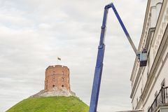 Gediminas tower on green hill, construction worker fixing house facade Stock Images