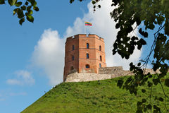 Gediminas Tower on green hill in Vilnius. Gediminas Tower on green hill with Lithuanian flag on top. The historical tower is made of red brick stock photos