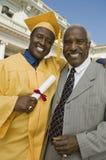 Gediplomeerde met vader buiten universiteit Stock Foto