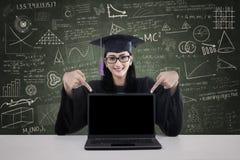 Gediplomeerde student die copyspace op laptop toont Stock Fotografie