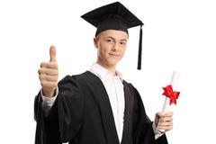 Gediplomeerde student die een diploma houden en een duim maken omhoog ondertekenen royalty-vrije stock fotografie