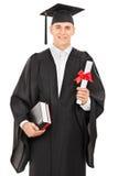 Gediplomeerde student die een diploma houdt Stock Foto's