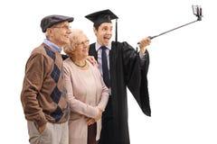 Gediplomeerde student die een selfie met zijn grootouders nemen stock foto's