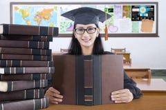 Gediplomeerde student die met baret in klasse bestuderen stock afbeelding