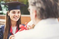Gediplomeerde student met haar vader stock fotografie
