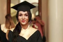 Gediplomeerde studenten die graduatiehoed dragen stock afbeeldingen