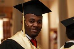 Gediplomeerde studenten die graduatiehoed en toga dragen royalty-vrije stock afbeelding
