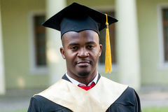 Gediplomeerde studenten die graduatiehoed en toga dragen stock foto's
