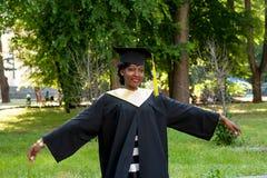 Gediplomeerde studenten die graduatiehoed en toga dragen royalty-vrije stock afbeeldingen