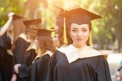 Gediplomeerde studenten die graduatiehoed en toga dragen stock afbeeldingen